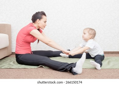 Mother and daughter practicing yoga at home