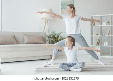 mother and daughter practicing yoga together