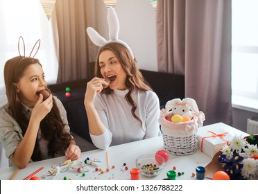 Mother and daughter prepare for breakfast. They sit together in room and eat chocolate eggs. Basket with decoration, paint and sweets on table.