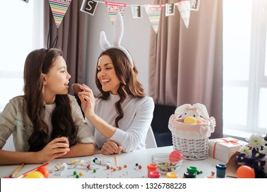 Mother and daughter prepare for Easter. They sit at table in room. Young woman feed girl with chocolate egg. Kid keep mouth opened. Decoration and paint with sweets on table.