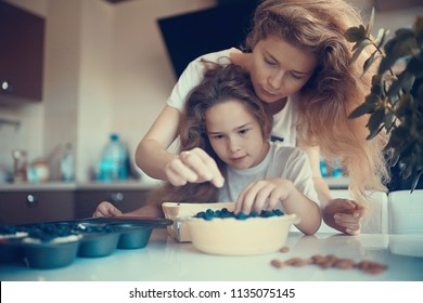 mother and daughter prepare a pie / home mom and daughter in kitchen bake a blueberry pie, the concept of  family home cosiness