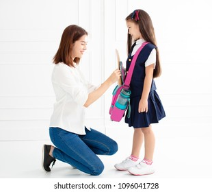mother and daughter preparing backpack for school