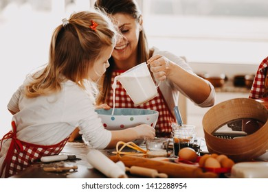 Mother and daughter preparing dough for cookies.