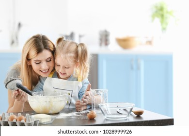 Mother and daughter preparing dough indoors