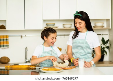 Mother and daughter preparing food, knead a dough. Staying at home at white kitchen, laughing and playing. Family leisure at home