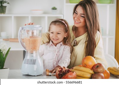 Mother and daughter preparing healthy fruit drink or meal in a blender in the kitchen.