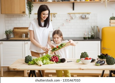Mother and daughter in preparing healthy vegetables  salad  together  in the kitchen. Help children to parents.