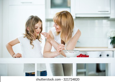 Mother and daughter preparing muesli with raspberries
