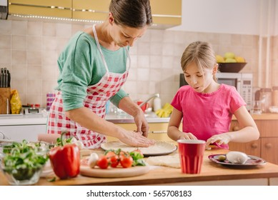 Mother and daughter preparing pizza in the kitchen