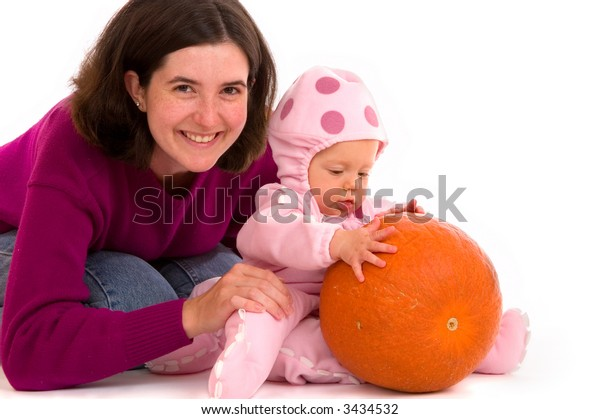 Mother and daughter with a pumpkin, for a Halloween portrait. Baby is wearing a pink octopus costume and exploring the pumpkin which she has never seen before.