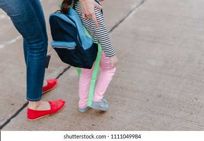Mother and daughter pupil walking together the first day going study back to school student concept at village street with schoolbag family lifestyle.