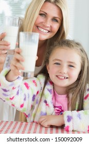 Mother and daughter raising milk glasses in kitchen