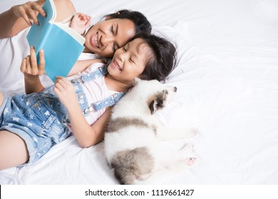 Mother and daughter read a book in her bed. And there is a dog lying down.