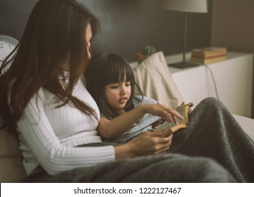 mother and daughter reading book at home in the bedroom