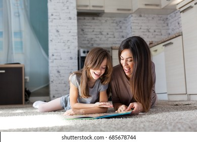 Mother and daughter reading book in the living room
