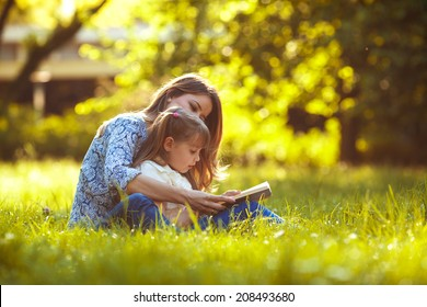 Mother and daughter reading a book at the park.