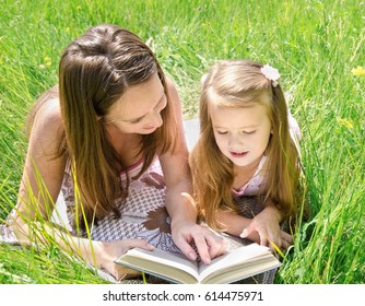 Mother with daughter reading a book in the park outdoor