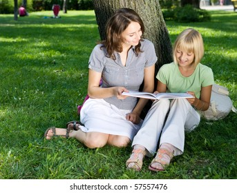 Mother and Daughter reading the Book in a park.Education concept