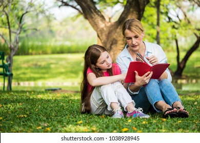 Mother and daughter reading a book together in a park. Family and education concept