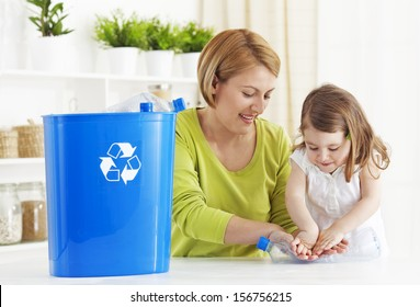 Mother and daughter recycling empty plastic bottle