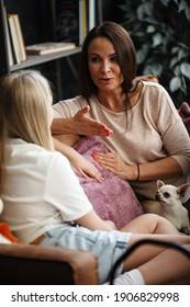 Konzept der Mutter-Tochter-Beziehung. Eine Frau und ein Teenagermädchen sitzen vor dem Fernseher auf dem Sofa und haben Spaß beim Sprechen. Die Familie verbringt Zeit zu Hause. Kleiner Hund, der auf Runden liegt.