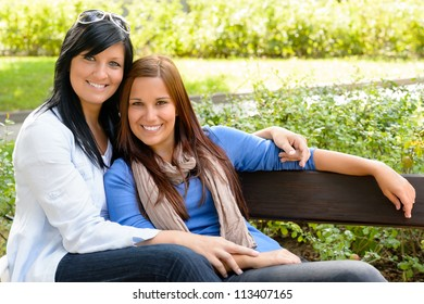 Mother and daughter relaxing on park bench happy bonding teen