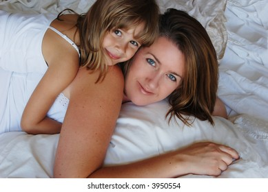 A mother and daughter relaxing together on a bed