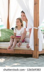 Mother and daughter resting on the beach in a bed with a veil