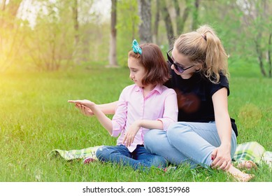mother and daughter resting on the nature on the green grass, resting, smiling in the summer in Sunny weather