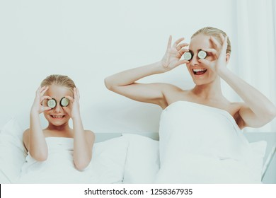 Mother With Daughter Are Resting. Spa Concept. Relaxing Together. Holiday Leisure. Cucumbers On The Eyes. Time To Chill Out. White Body Towels. Smiling Family Weekend. Soft Pillows.