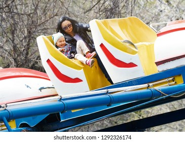 Mother and daughter riding on the child rollercoaster. Amusement park for the children