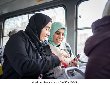 Mother and daughter riding public transport in city