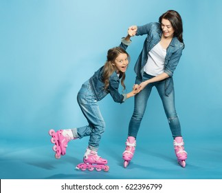 mother and daughter in roller skates having fun in studio on blue