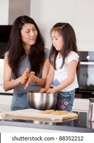 Mother and daughter rolling cookie dough together in kitchen