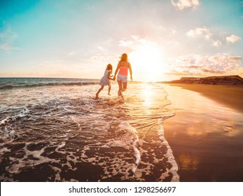 Mother and daughter running inside the water on tropical beach - Mum playing with her kid in holiday vacation next to the ocean - Family lifestyle and love concept - Focus on bodies silhouette