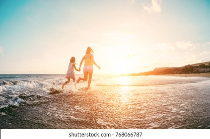 Mother and daughter running inside the water on tropical beach - Mum playing with her kid in holiday vacation next to the ocean - Family lifestyle and love concept - Focus on silhouettes