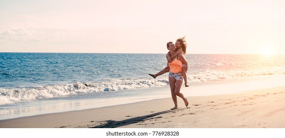 Mother and daughter running next the water on tropical beach - Mum playing with her kid in holiday vacation - Family lifestyle and love concept - Focus on bodies