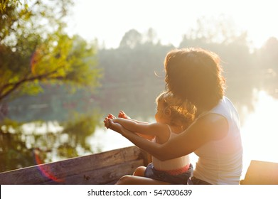 Mother and daughter sailing in a wooden boat. Sunset, sun glare on the photo.