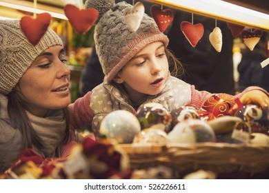 mother and daughter selecting decoration on a Christmas market
