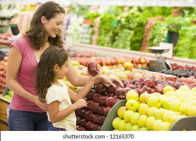 Mother and daughter shopping for fresh produce in supermarket [approx. 7 years old]