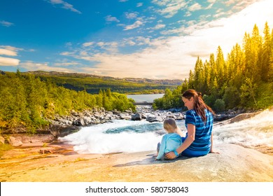 mother and daughter sit on the banks of the crystal clear mountain river. Travel Norway, Lofoten