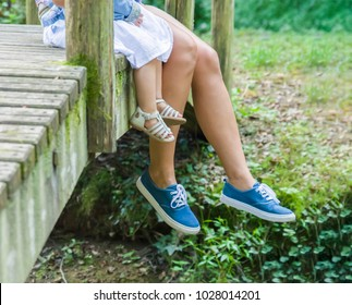 Mother and daughter sit on the wooden bridge and hanging legs