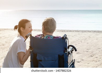 Mother and daughter sit together in front of the beach looking at each other.  This shows the happiness and love in family. This can be related with any article about family, elder, health.
