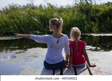 Mother and daughter sits on a wooden bridge with feet in the water