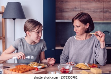 Mother and daughter sitting by the table and having lunch at home