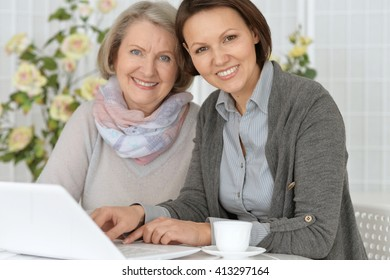 mother and daughter sitting at the computer and drinking tea