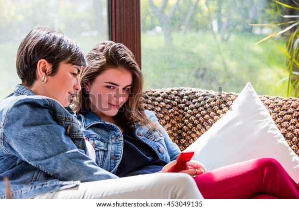 Mother and daughter sitting in a couch looking at the daughters smartphone.