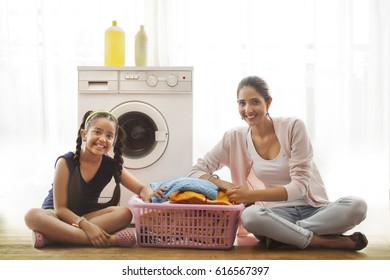 Mother and daughter sitting in front of washing machine with laundry basket