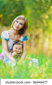 Mother daughter sitting grass next summer park