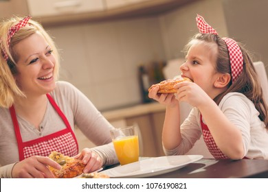 Mother and daughter sitting in the kitchen, eating pizza and having fun. Focus on the daughter